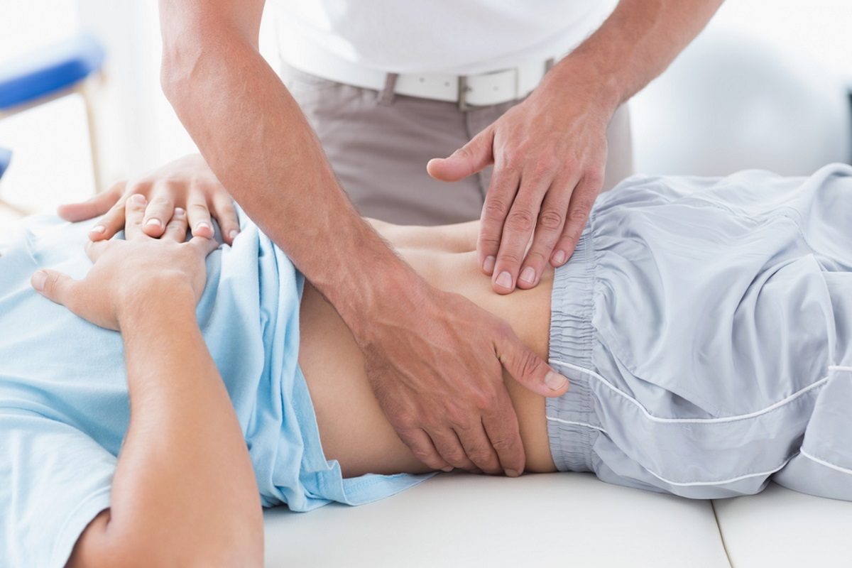 Doctor Massaging female patient's stomach